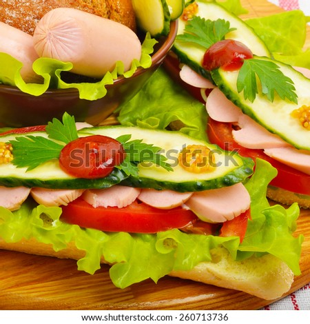 Big appetizing fast food baguette sandwich with lettuce, tomato and frankfurter on the board. Junk food