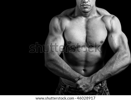 Big athletic man showing his muscles over black background - stock photo