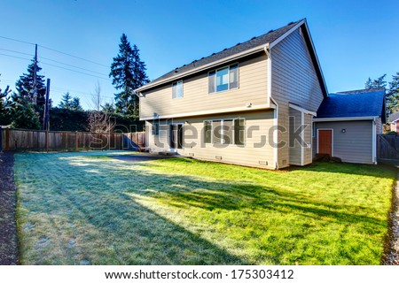Big backyard with small concrete patio area and  green lawn - stock photo