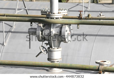 big ball valve above the huge gas pressure vessel in the system of natural gas storage in the industrial refinery