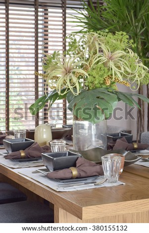 Big beautiful vase with green flower setting with modern dining set on wooden table