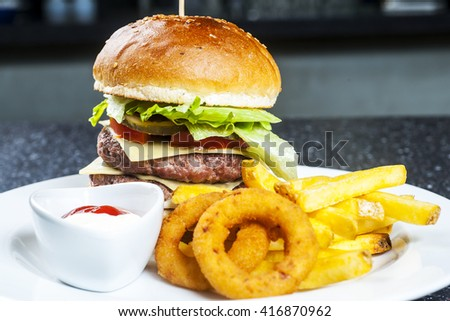 Big beef burger with onion rings and french fries.Selective focus on the burger - stock photo