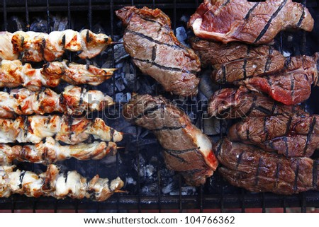big beef steak on grilling grid over barbecue charcoal - stock photo