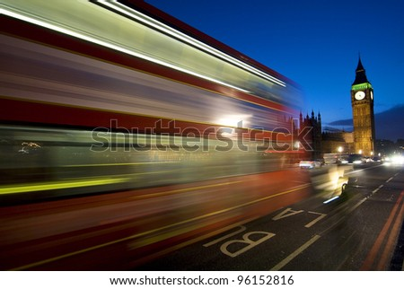 Big Ben and Houses of Parliament at night with moving double decker bus, London, UK.