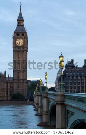 Big Ben and illuminated bridge in the early morning in London, natural colors and lights - stock photo