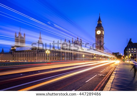 Big Ben and London at night with the lights of the cars passing by. - stock photo