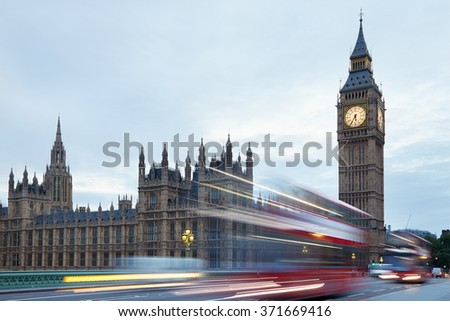 Big Ben and Palace of Westminster in the early morning, red buses passing in London, natural colors and lights - stock photo