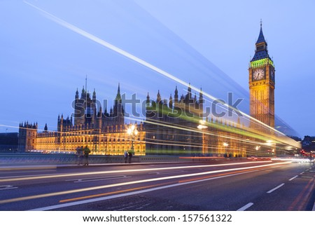 Big Ben and the Houses of Parliament illuminated at night in London, England. The lights of passing cars can be seen in the photo. - stock photo