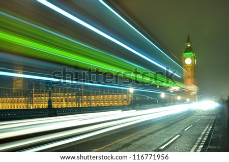 Big Ben at night along with the lights of the cars passing by - stock photo