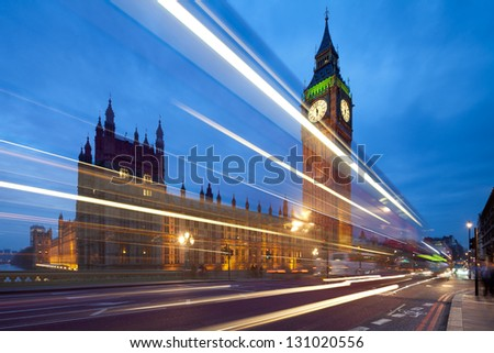 Big Ben in the evening. Dabldekker passes and leaves a line of light at slow shutter speeds. Cityscape shot with tilt-shift lens maintaining verticals - stock photo