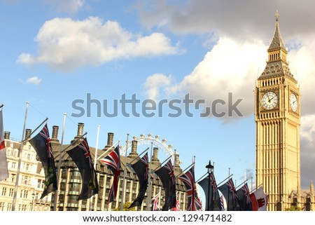 Big Ben, London Eye and British flags from Parliament Square by day, London, United Kingdom. - stock photo
