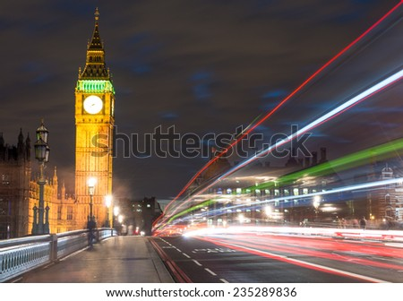 Big Ben, one of the most prominent symbols of both London and England, as shown at night along with the lights of the cars passing by - UK