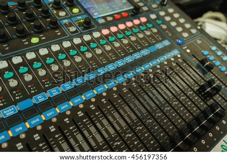 Big black professional mixer with buttons and sliders to control the audio output power amplifier and speakers.