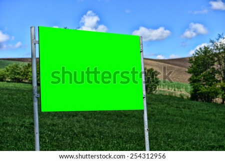 Big blank and green billboard in the nature. Copy space - stock photo