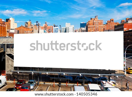 Big blank billboard in New York City, surrounded by highrise buildings and a bright blue sky overhead - stock photo