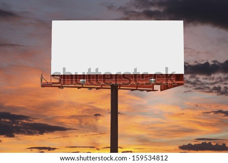 Big blank billboard with orange sunset sky.