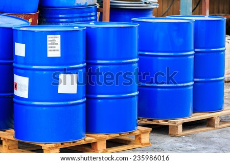 Big blue barrels standing on wooden pallets on a chemical plant - stock photo