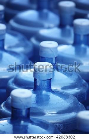 Big blue reusable water bottles background. Shallow DOF. - stock photo