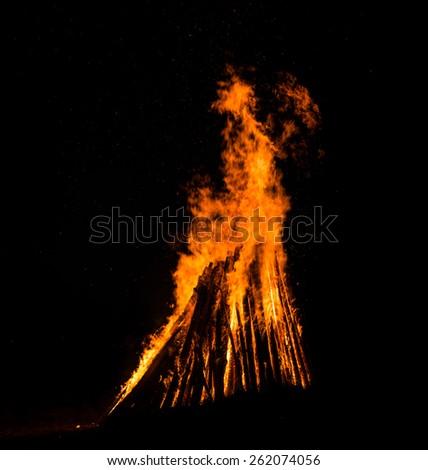 Big bonfire against dark night sky.  Fire flames on black background - stock photo