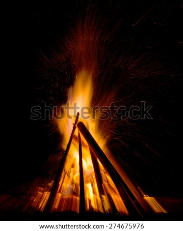 Big bonfire against dark night sky. Fire flames on black background