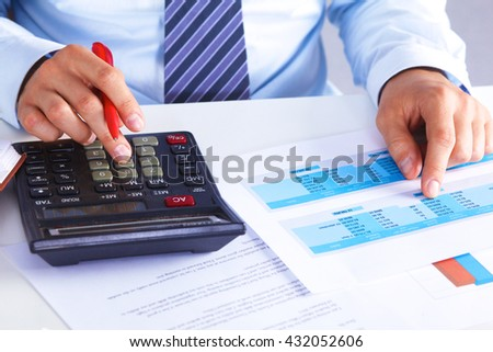 Big boss checks calculations on a calculator - stock photo