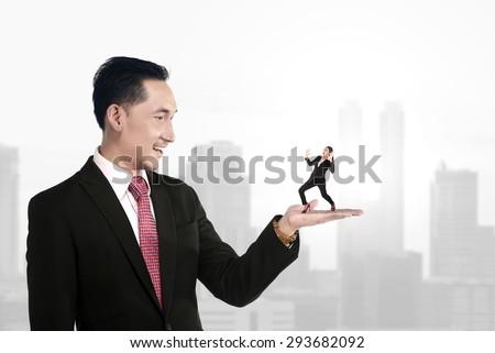Big boss holding small subordinate, management concept - stock photo