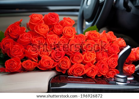 Big bouquet of beautiful red roses in luxury car. Composition for a romance or anniversary - stock photo