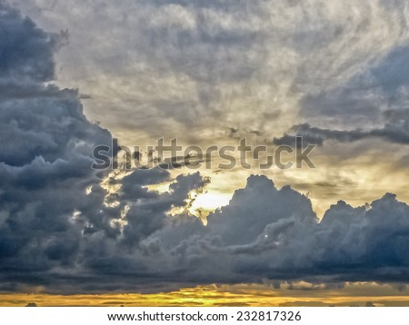 Big breathtaking clouds with the sun behind sunset landscape view in warm tones. - stock photo