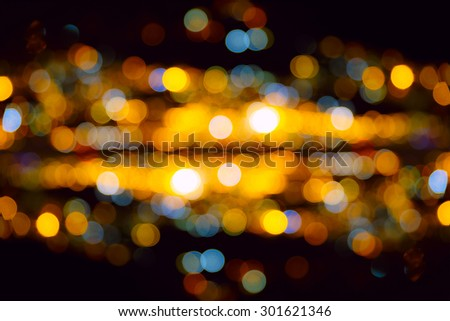 Big bright round defocused colored lights on black background - stock photo