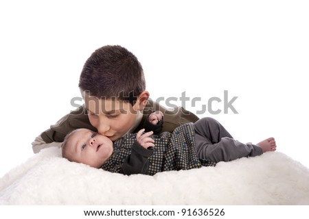 big brother giving a kiss at this baby sister. isolated on white background - stock photo