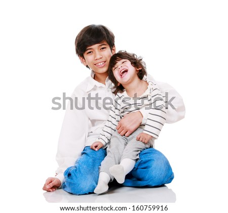 Big brother holding disabled two year old child. Child has cerebral palsy. - stock photo