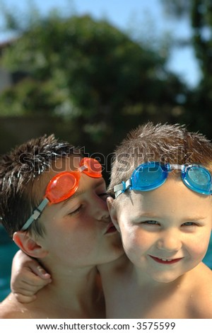 Big brother smooching his baby brother on the cheek while swimming - stock photo