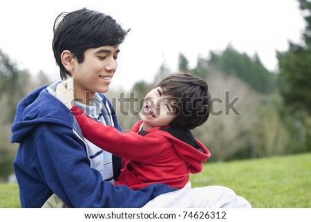 Big brother taking care of disabled little brother - stock photo