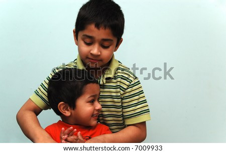 Big brother taking care of the smaller kid - stock photo