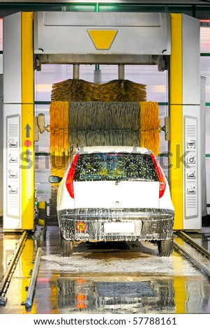 Big brushes scrubbing the car in automatic carwash - stock photo