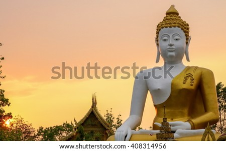 Big Buddha statue in Thailand temple with sunset background - stock photo