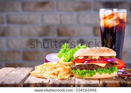 Big burger in classic american style with hot grilled patty with melted cheese on top, tomato, onion, sauces and french fries with cold soft drink served on wooden table.