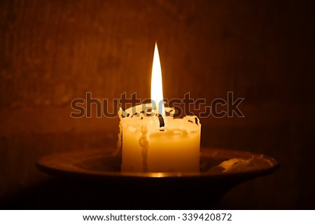 Big burning candle in a dim church - stock photo