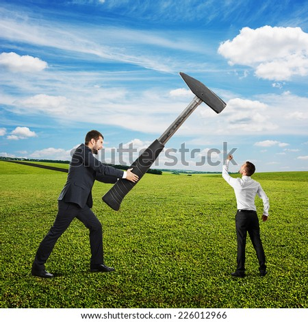 big businessman holding hammer, small businessman showing fist and screaming. photo at outdoor - stock photo