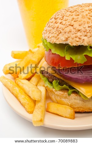 big cheeseburger garnished with french fries on a  plate and a glass of lemonade on white background - stock photo