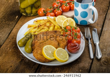 Big Chicken schnitzel with homemade chilli french fries, cherry tomatoes, pickels and grapes fresh - stock photo
