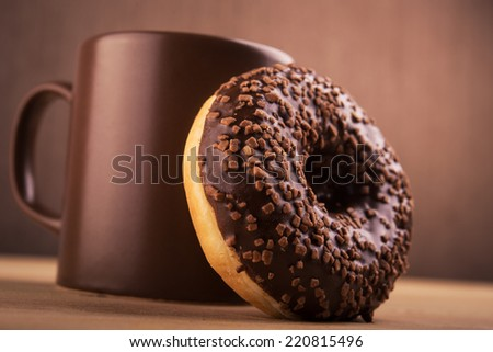 big chocolate donut and cup of coffee - stock photo