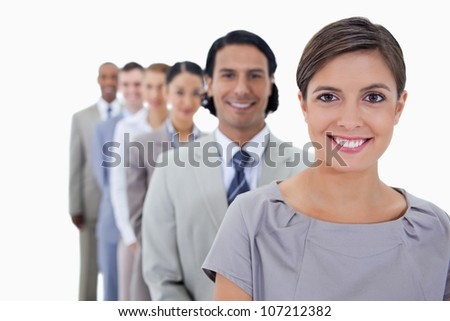 Big close-up of colleagues in a single line smiling and looking straight with focus on the first woman against white background