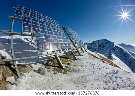 Big cluster of solar panels on a mountain peak - stock photo