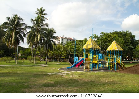 Big colorful children playground equipment in middle of park - stock photo