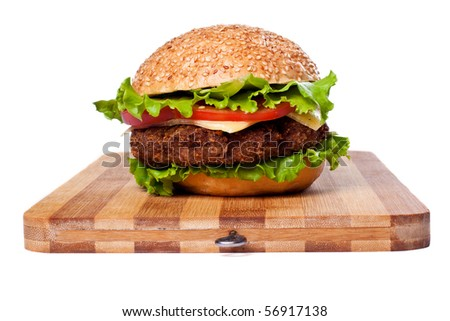 Big colorful hamburger on chopping board  isolated on white - stock photo