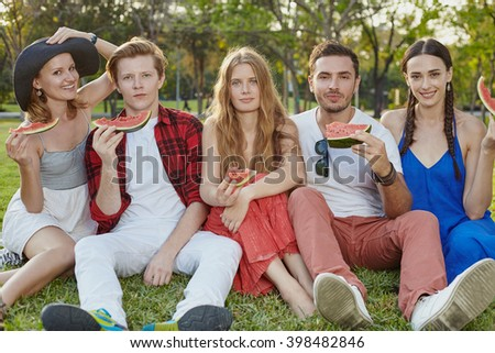 Big company of young people sitting on the grass in the park - stock photo