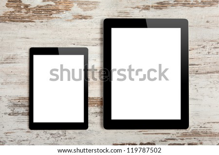 big computer and mini tablet with isolated screen on a background of wood - stock photo