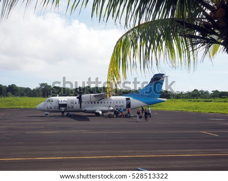 BIG CORN ISLAND, NICARAGUA-AUG. 27: Tourists disembarking from twin prop plane on tarmac airport of Big Corn Island, Nicaragua, Central America on August 27, 2016.