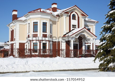 Big cottage with red roof and white drain at frosty and sunny winter day. - stock photo